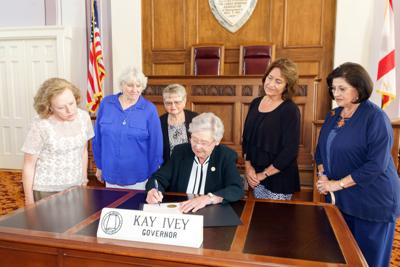 Five members of three garden clubs in Alabama watch as Alabama Governor Kay Ivey signs the Proclamation that designates the week of June 2-8, 2019 as National Garden Week by the National Garden Clubs, Inc. Left to right, Joyce Turnipseed, member of Chunnenuggee Garden Club of Union Springs; two members of the Camellia Garden Club of Clayton, Jolene Gothard and Betty Lee; and two members of the Georgiana Garden Club, Judy Manning and Suzy Shepherd. The Proclamation is an effort to acknowledge the importance of Gardening and the numerous contributions of Gardeners.