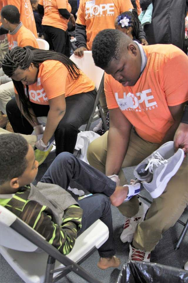 Jo Kyle Smith putting shoes on the feet of a child.