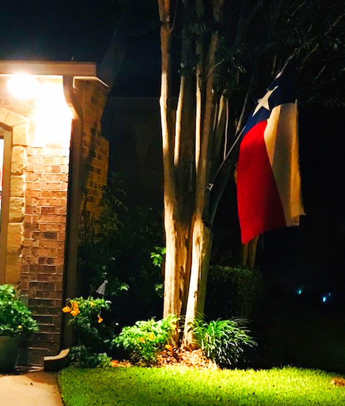 Security flood light at garage with Texas Flag