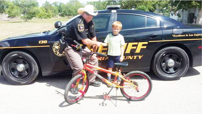 Deputy Scott Barton with Micah Adams and his recovered bike