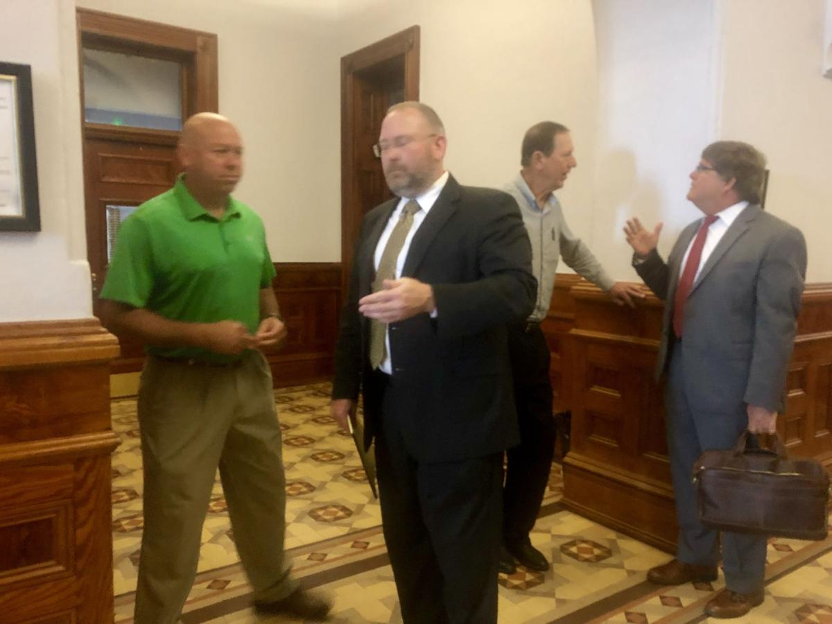 Hallettsville high assistant principal Scott Cottenoir talks with his attorney
