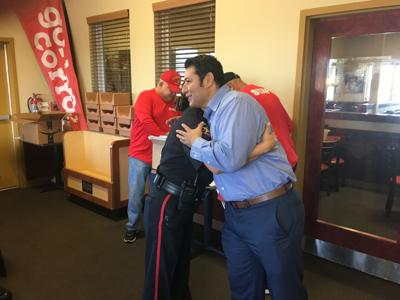 Mark Longoria hugs a volunteer with the Victoria Police Department at the Toys for Tots kick off breakfast.