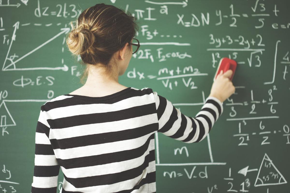Young student cleaning green chalkboard with duster  in classroom (copy)