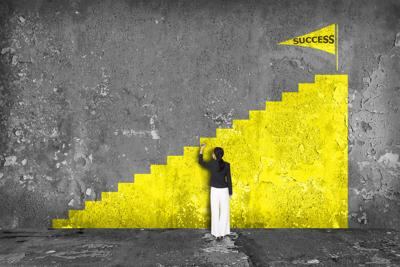 businesswoman drawing  ladder of success on the wall