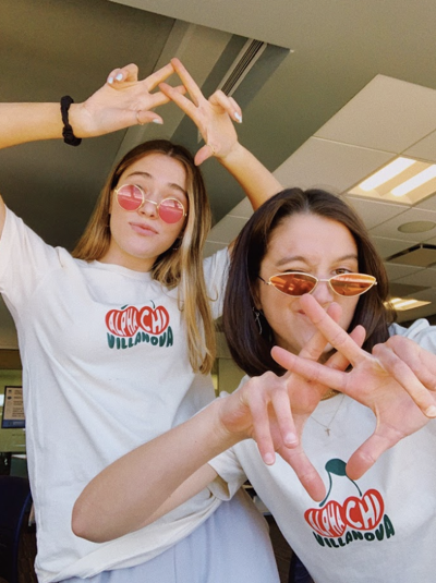 Alpha Chi Omega sisters Abigail Lukas (left) and Elena Rouse (right) do their sorority hand sign during recruitment partner rounds.