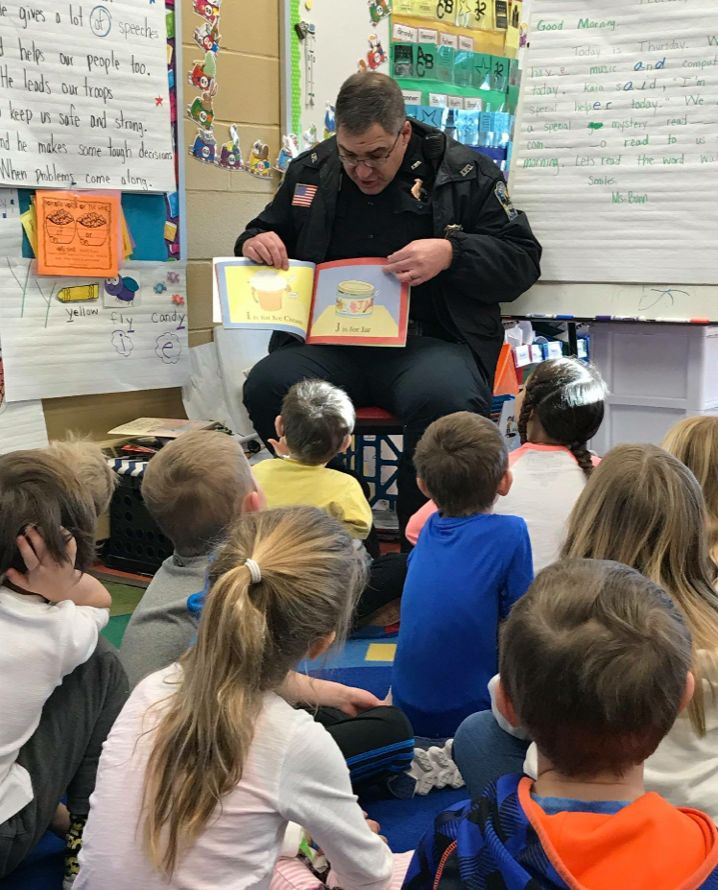 Officer Gripne reads to kids in one of the Alexandria Public Schools