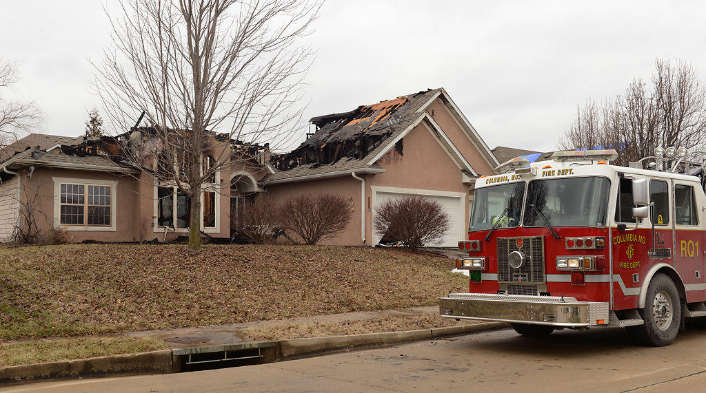 Fire truck sits outside of charred house