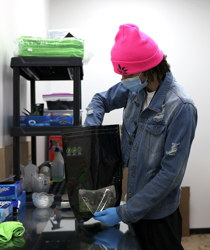 A Green Releaf employee packages 3.5 grams of Bubba Fett marijuana into a bag