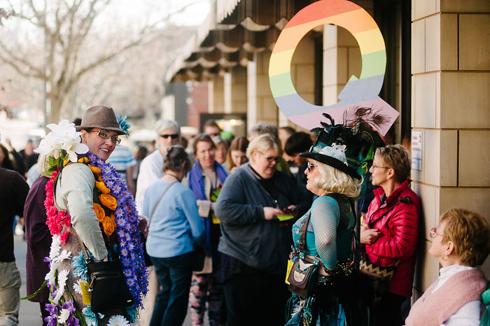 Fest-goers stand in the Q line and mingle outside the Missouri Theatre