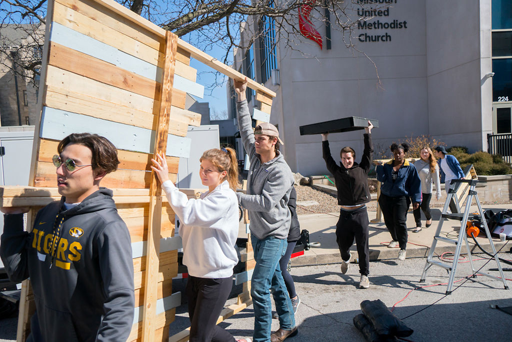 Volunteers and artists assemble the art installations