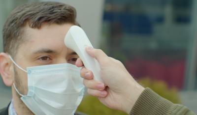 man in mask having temperature check-coronavirus