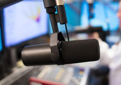 Studio Microphone in Radio Station with Female Host In Background