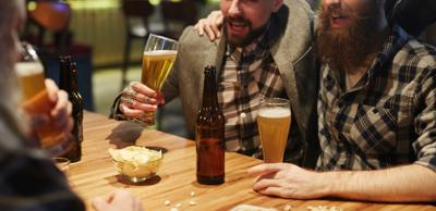 Drunk buddies cheering with beer and talking by table in pub- bar- beer-generic