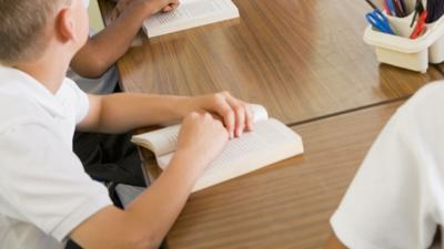 Schoolchildren and their teacher reading books in class