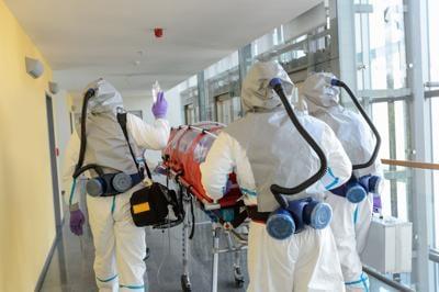 Biohazard team pushing stretcher in hospital