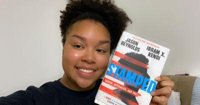 """Preservice teacher Hope Wilson with young adult book """"Stamped."""