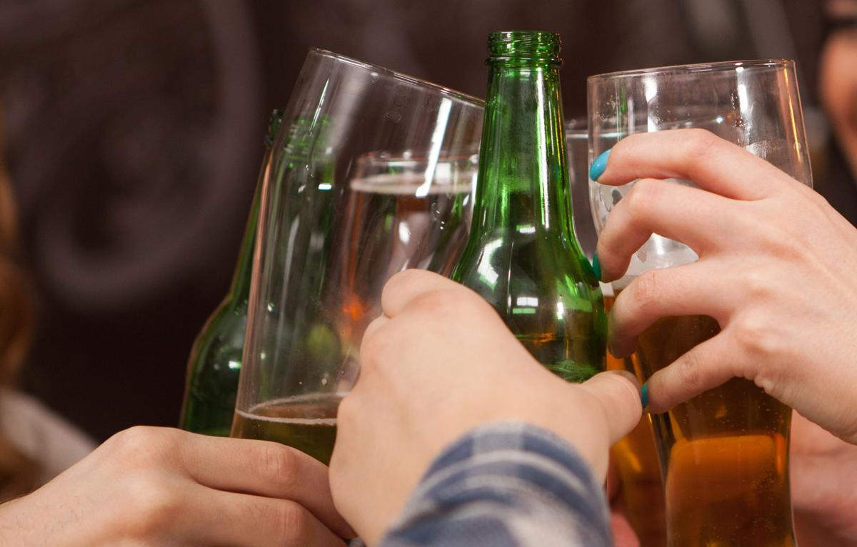 Happy young friends clinking beer bottles in vintage old styled pub