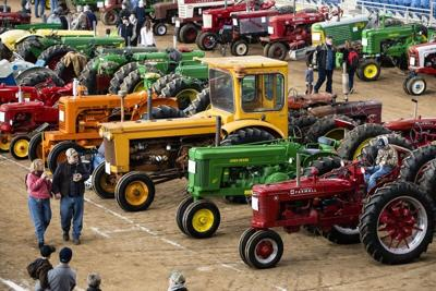 ILE - In this Jan. 8, 2020 file photo visitors view antique tractors during the 104th Pennsylvania Farm Show in Harrisburg, Pa. The massive annual Pennsylvania Farm Show was canceled as an in-person event on Wednesday, Aug. 19 because of the pandemic, ending the prospect of hundreds of thousands of people converging on the Harrisburg complex in January. (AP Photo/Matt Rourke, File)