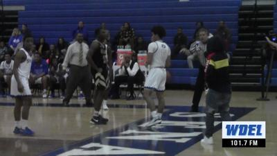 A spectator walks close to the court to shoot video at a Dover High School game