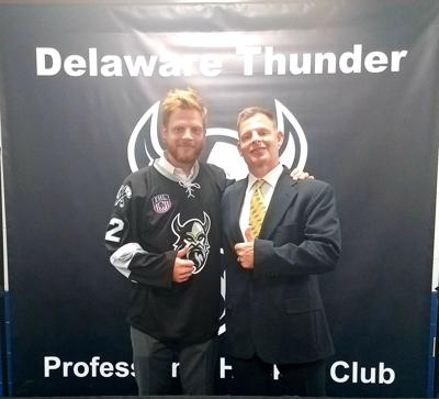 Charlie Pens, Jr. (left) signs a contract to play with the Delaware Thunder