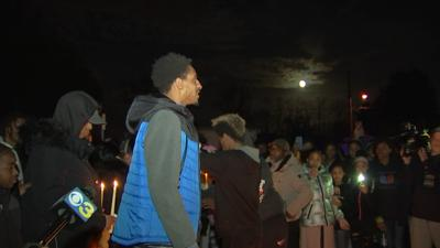 Aki Newman addresses the crowd during a candlelight vigil for Jordan Tate