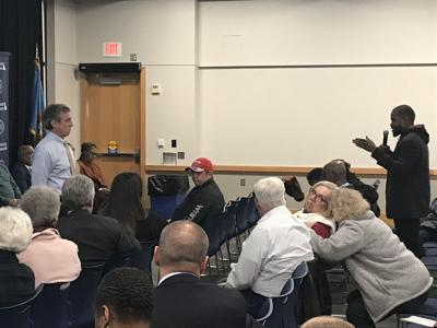 Delaware Governor John Carney hears from a resident during a town hall on February 19, 2020