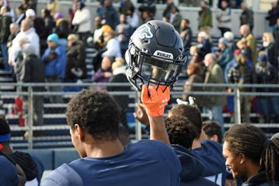 A Wesley football player holds up his helmet before a 2019 game