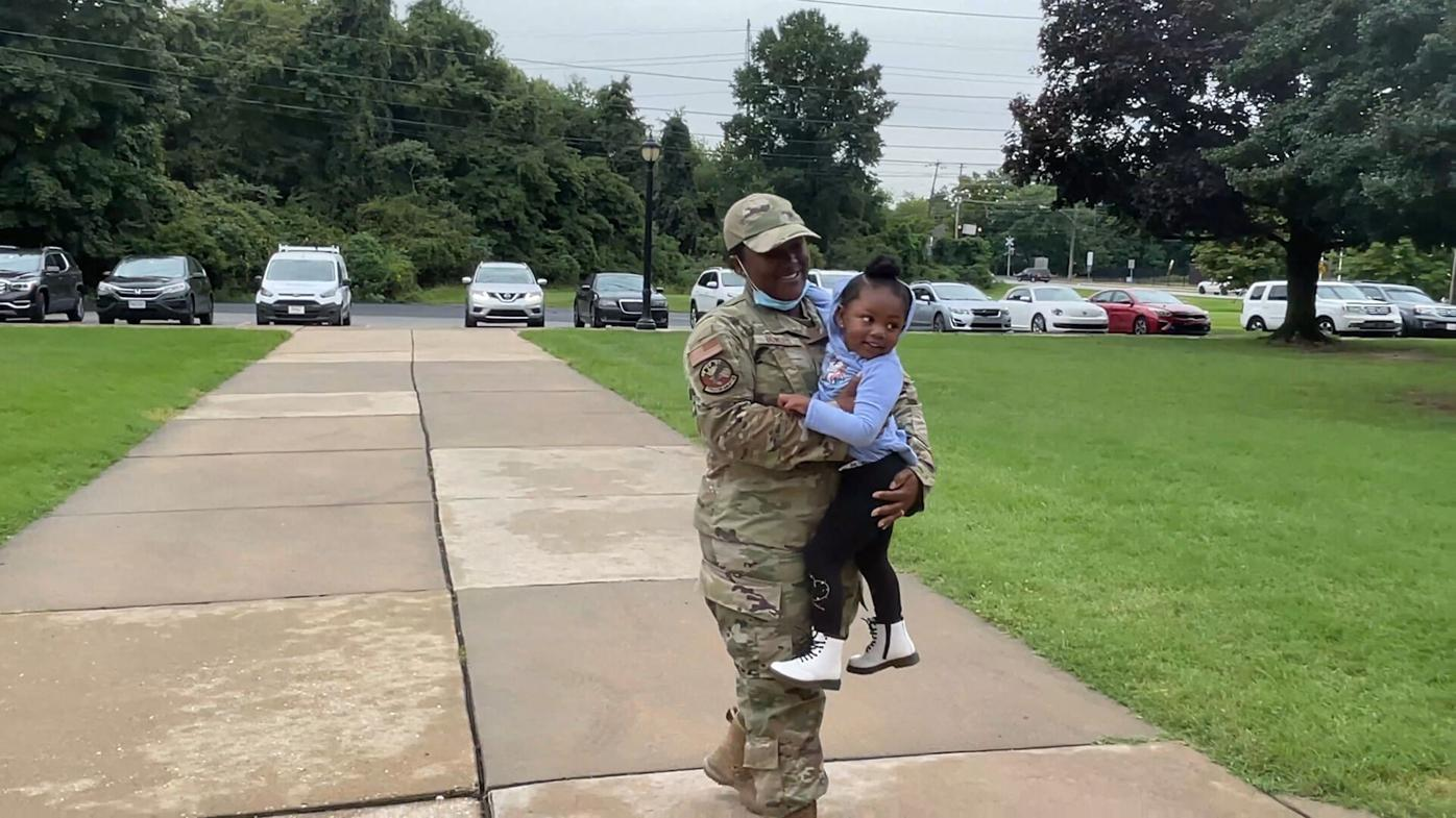 Delaware Air National Guard Staff Sergeant Alexys Bowers hugs her daughter Alani after returning home from Kuwait