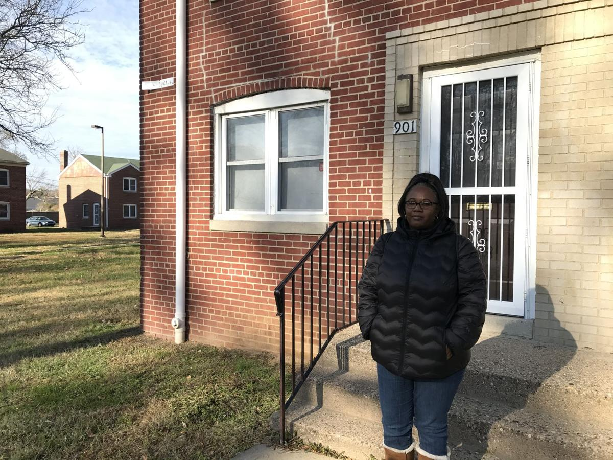 Michelle Robinson stands in front of her Southbridge house, one that has multiple groups of mold spores