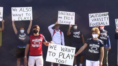 Salesianum football players hold up signs during a protest before practice on Wednesday, October 14, 2020