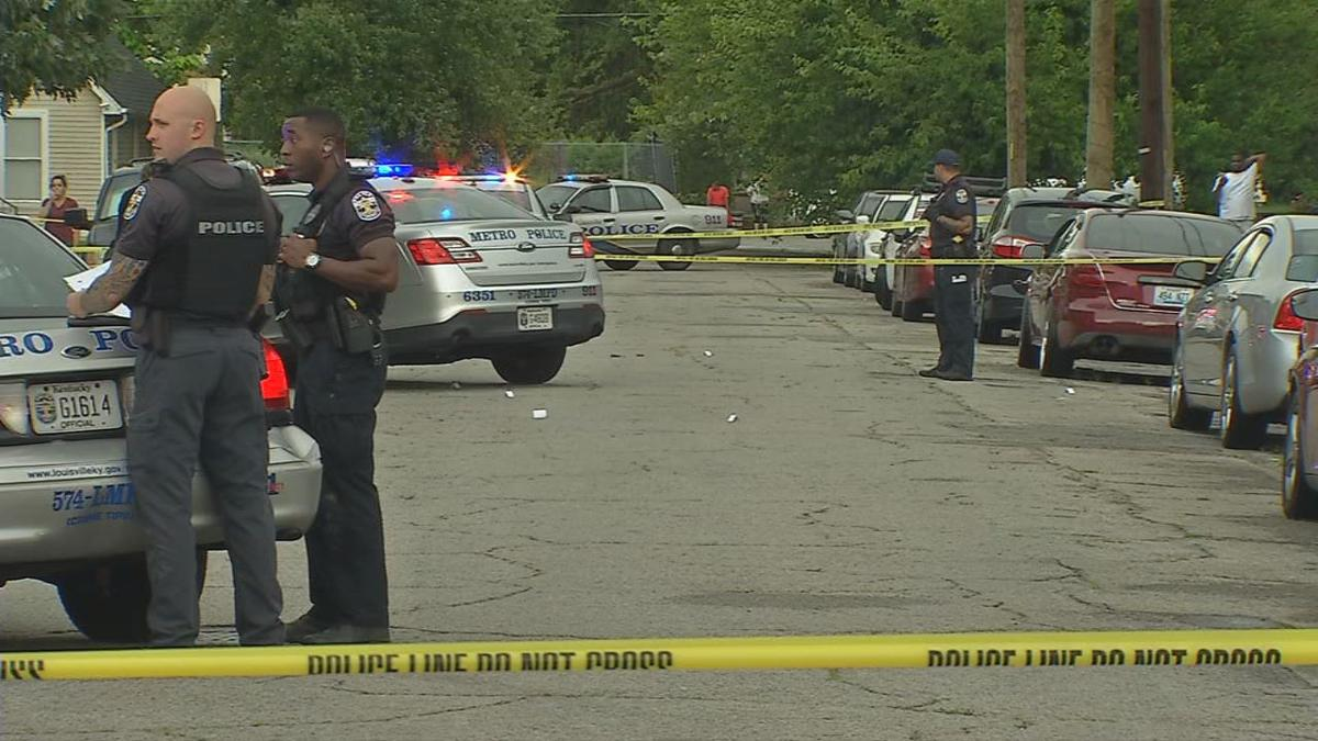 LMPD officers at crime scene behind police tape in the daytime