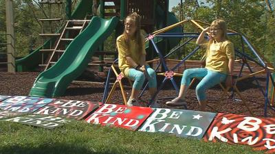 Sisters Raegan and Rylyn Richins in front of their 'Be Kind' signs