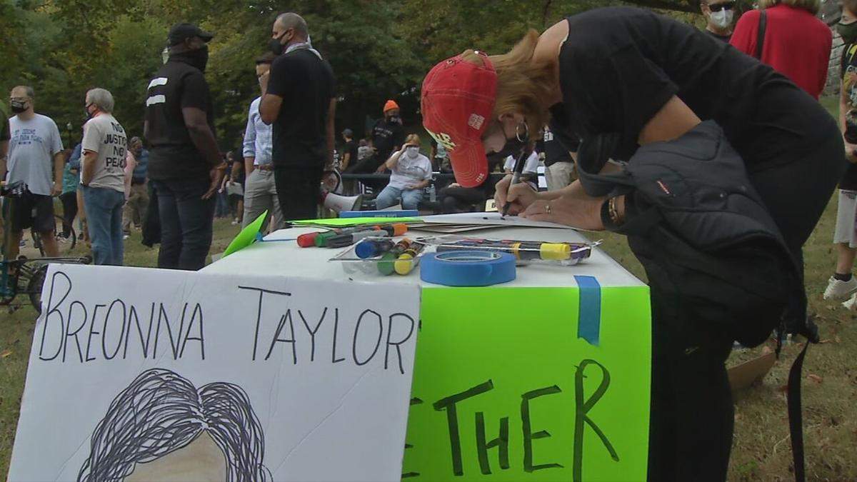 Woman makes sign during rally at Tyler Park 10-10-20
