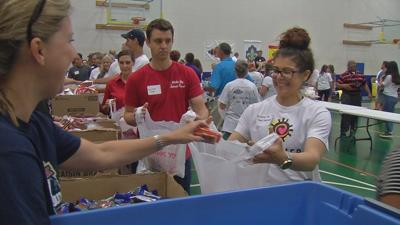 Volunteers pack thousands of meals for low-income Louisville children to eat during the summer