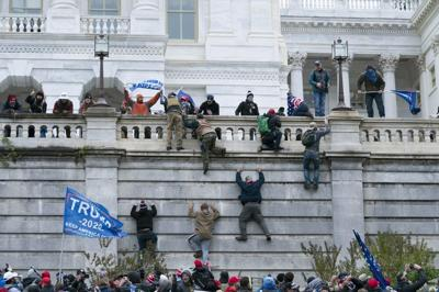 Supporters of President Donald Trump climb the west wall of the the U.S. Capitol on Wednesday, Jan. 6, 2021