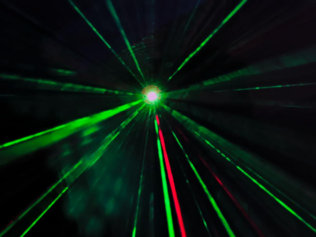 laser beams in green and red colors reflecting in the mist