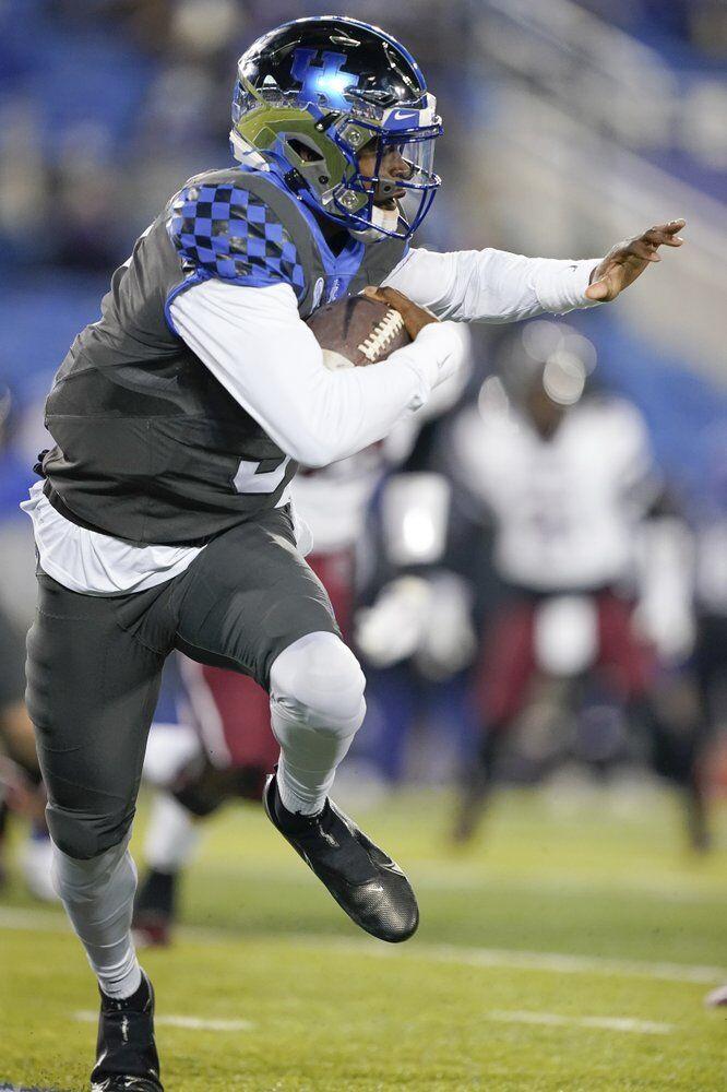Kentucky quarterback Terry Wilson scrambles with the ball