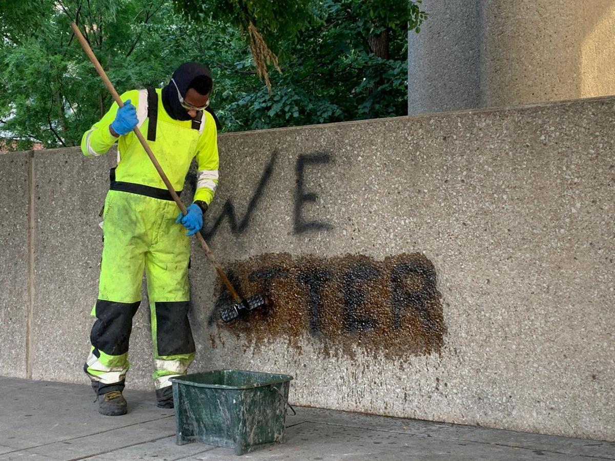 LMPD Protest - Worker cleans we matter graffiti at Hall of Justice