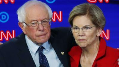 Sanders with arm around Warren