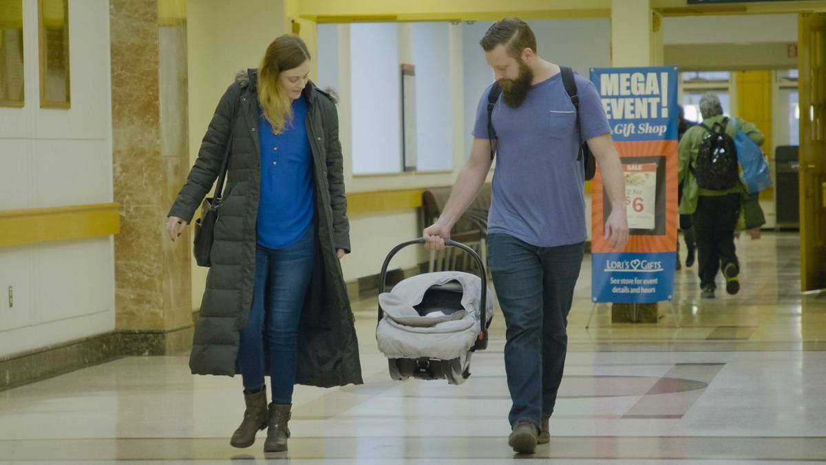 Jennifer Gobrecht and husband walk with baby in carrier