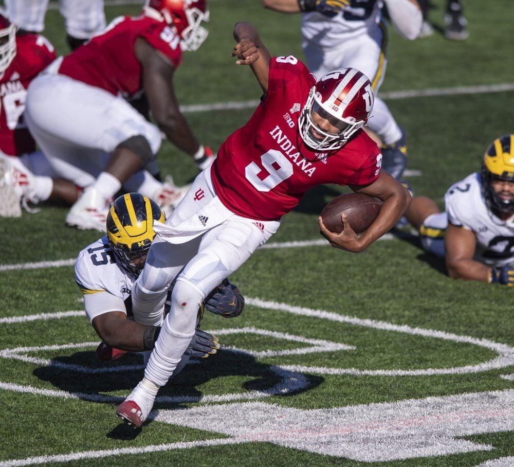 Indiana quarterback Michael Penix Jr. (9) is tripped up by Michigan defensive lineman