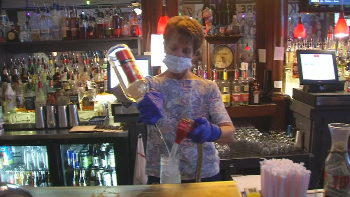 A bartender mixes a drink at The Back Door in Louisville, Ky.