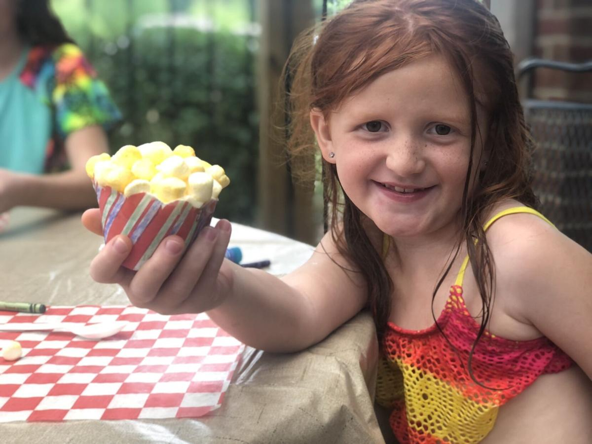 Girl decorates cupcake at Let's Get Crafty! event