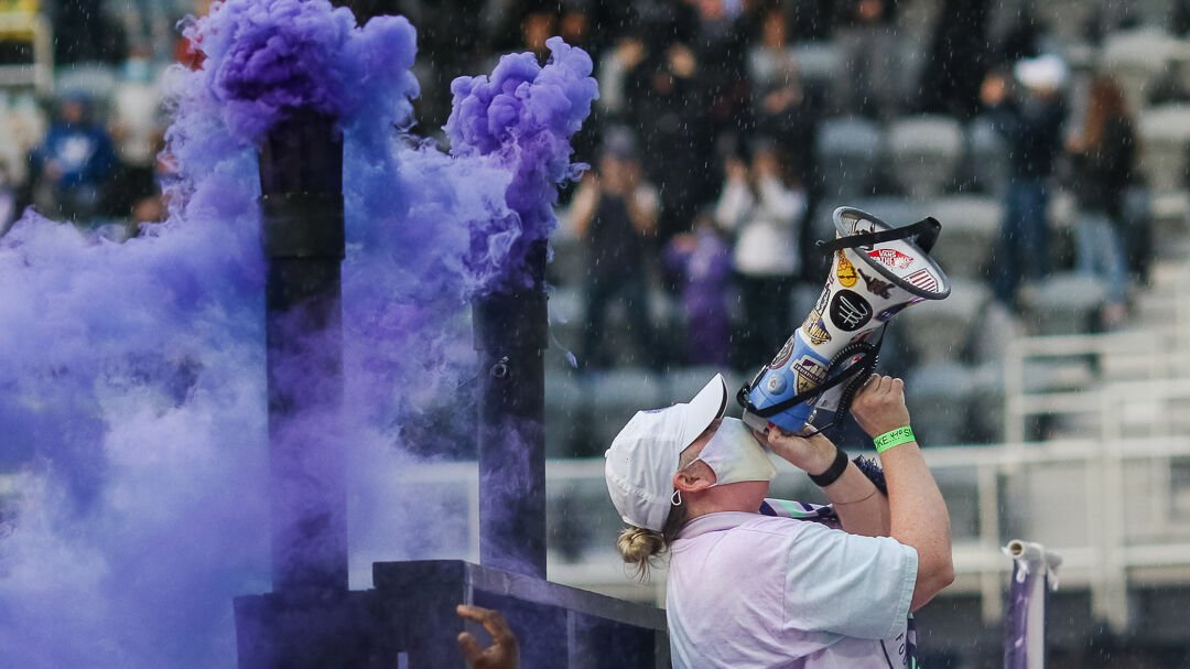 A Racing Louisville FC supporter cheers through a megaphone