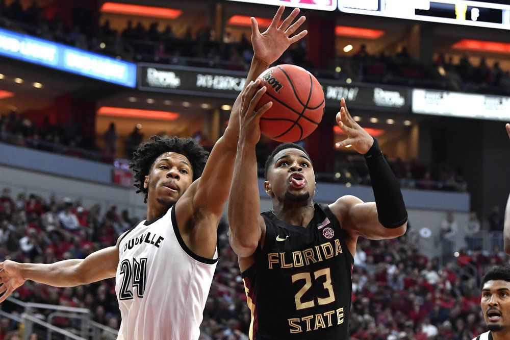 Florida State guard M.J. Walker (23) attempts to shoot past the defense of Louisville forward Dwayne Sutton