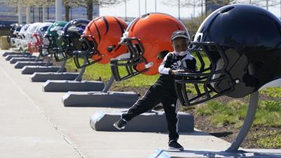 Child plays near 32 NFL team helmets on display in Cleveland