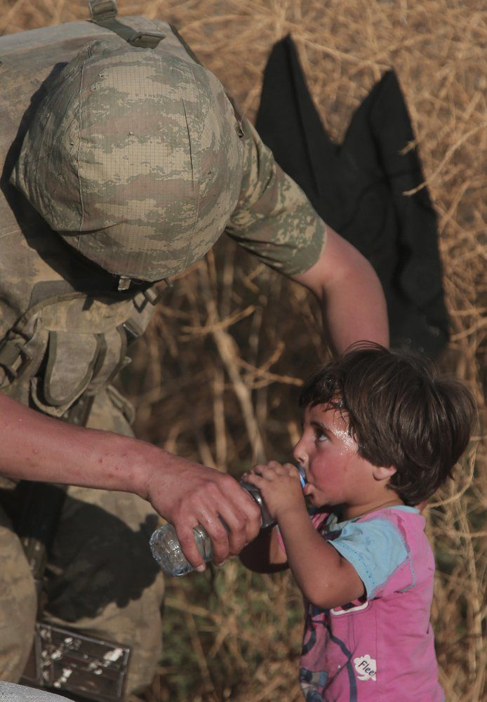 Turkish Soldier gives toddler water