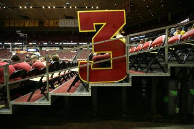A large 3-point sign sits in the stands before a college basketball game