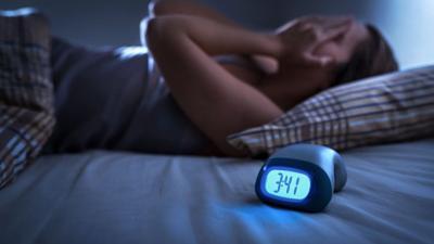 Poor sleep - Woman lying in bed near alarm clock