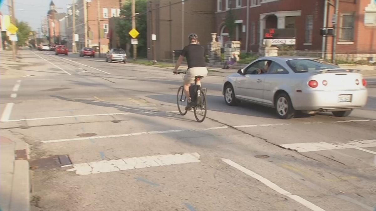 A man travels by bike through Louisville, Ky.